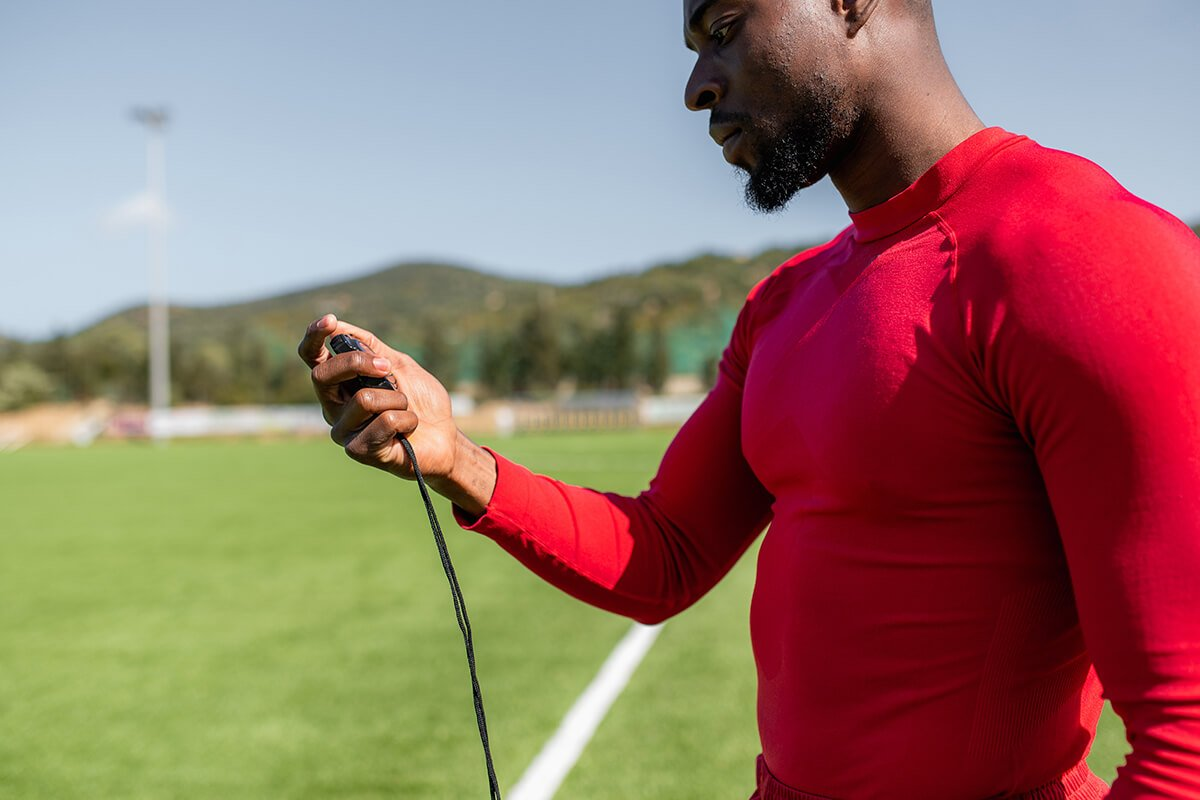 A Man in a Red Top Holding a Stop Watch on a Sports Field