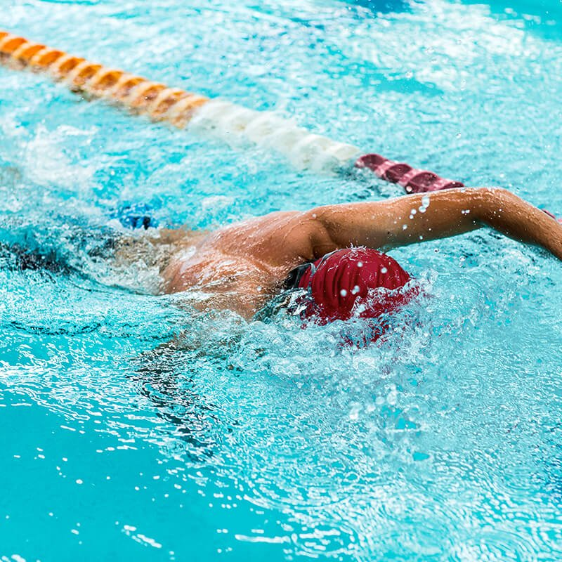 A Person in a Red Hat Swimming in a Pool